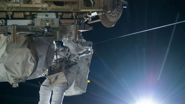 NASA astronaut Terry Virts is seen working to complete a cable routing task while the sun begins to peak over the ...