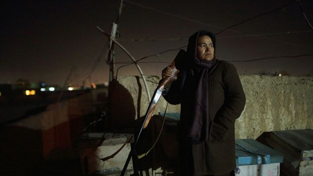 Sara Bahayi stands guard on the roof of her home.