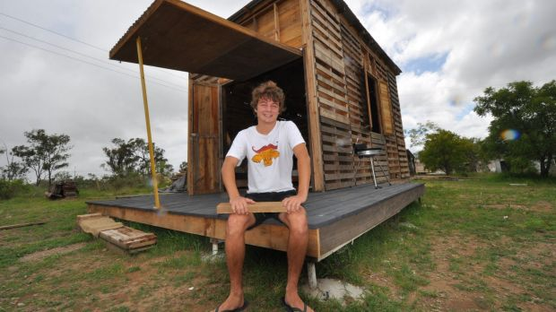 Angus Hughes with the prototype pallet house he built outside Rockhampton over five months.