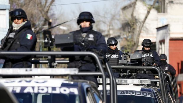 Federal police officers stand on the back of pick-up trucks while leaving a building housing the Assistant Attorney ...