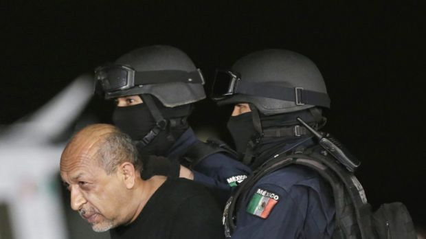 """Mexico's most-wanted drug lord Servando """"La Tuta"""" Gomez is escorted by police officers during a media conference about ..."""