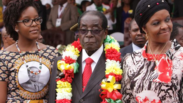 Zimbabwe's President Robert Mugabe is flanked by his daughter Bona and wife Grace during celebrations to mark his 91st ...