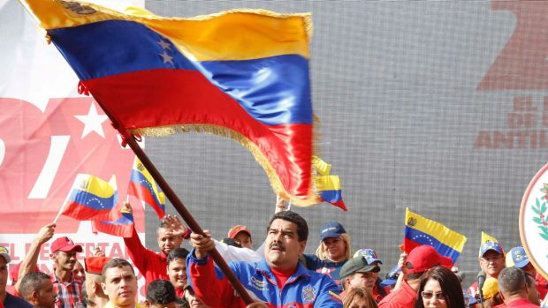 Venezuela's President Nicolas Maduro (C) waves a Venezuelan flag during a rally in February to commemorate the 26th ...