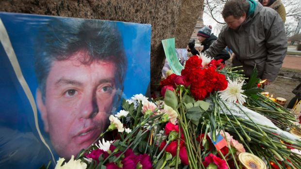 People lay flowers in memory of Boris Nemtsov at the monument of political prisoners 'Solovetsky Stone' in central St. ...
