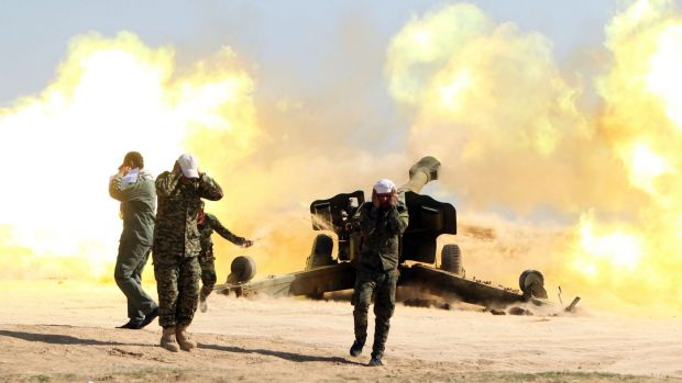 Volunteer Shiite fighters fire an artillery canon near the city of Tikrit.
