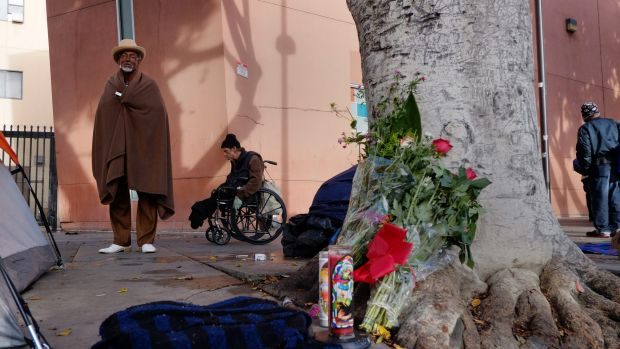 Ceola Waddell, 58, left, a homeless man who says he witnessed the police shooting on Skid Row on Sunday, stands by a ...