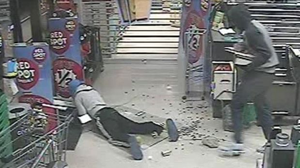 A screen grab from a CCTV video showing one of the men tripping and falling as he tries to flee with cash.