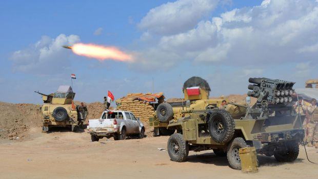 Iraqi government forces and allied militias fire against IS militants.
