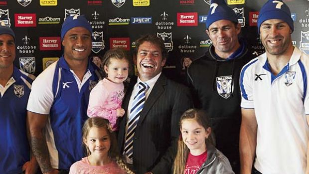 Time to go ... Brett Kimmorley, flanked by  his teammates and his daughters Ava, Mia and Maddi, announced his retirement ...