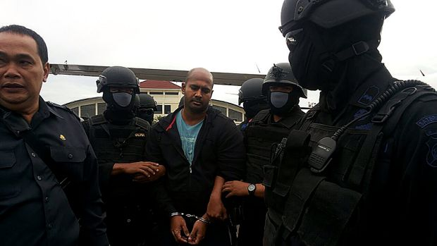 Myuran Sukumaran is surrounded by masked security personnel upon arriving at Cilacap airport.