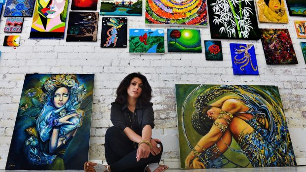 Leila Ashiani, an Iranian artist who survived the sinking of a boat carrying asylum seekers, with two of her works.
