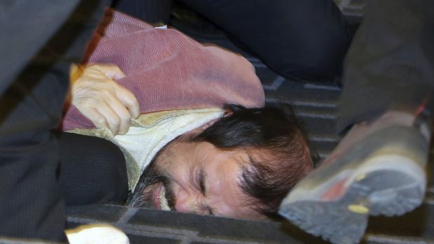 Security personnel detain the alleged assailant who attacked the US ambassador.