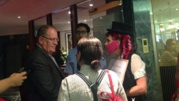 Female protesters dressed as men try to enter Brisbane's Tattersall's Club.