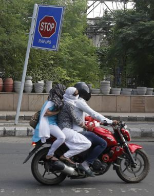 Commuters ride past an anti-rape sign in New Delhi.