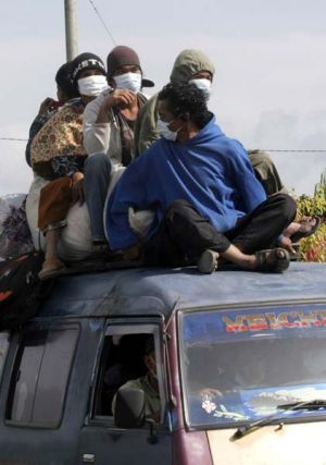 Escape . . . evacuated residents ride on the top of a van.