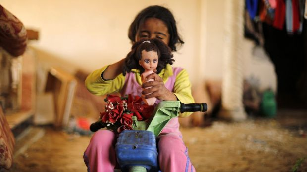 A Palestinian girl plays with a doll inside a destroyed building in Beit Hanun in the northern Gaza Strip.