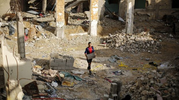 A man carries bricks amid the rubble of destroyed buildings in Beit Hanun in the northern Gaza Strip. A humanitarian ...