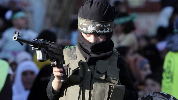 A Palestinian boy wears the headband of Hamas' armed wing and holds a toy gun during a rally in Gaza's Bureij refugee ...
