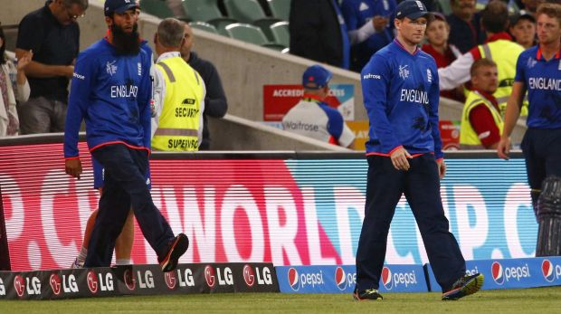 A dejected England opener Moeen Ali and captain Eoin Morgan walk onto the field after the game ended.