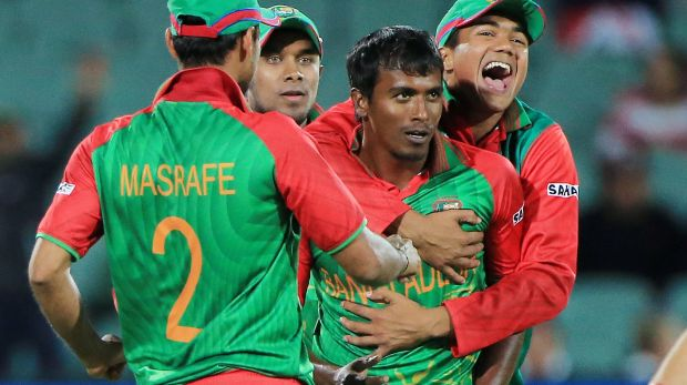 Match winner: Rubel Hossain is embraced by teammates after dismissing Eoin Morgan   in Adelaide.