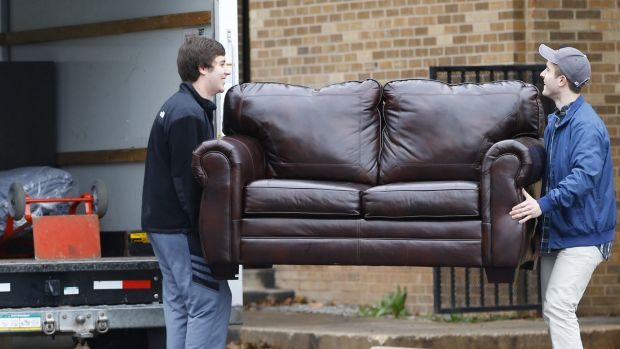 Two men load a couch from the now closed University of Oklahoma's Sigma Alpha Epsilon fraternity house into a moving ...