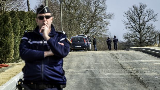 A gendarme stands guard near the site where the thieves attacked the vans.