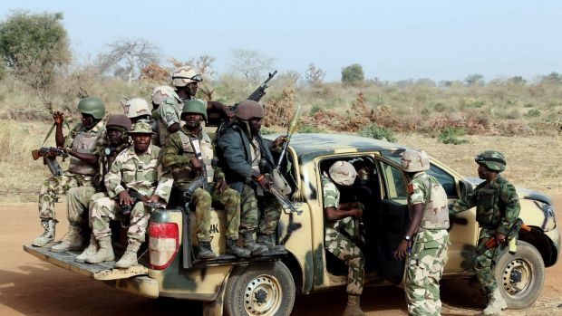 Nigerian army soldiers on patrol along a road in Chibok, northeastern Nigeria, near where more than 200 girls were ...