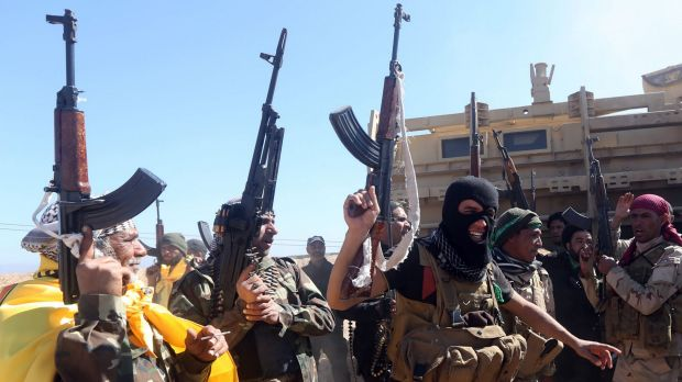 Iraqi pro-government fighters celebrate as they advance into Tikrit on Wednesday.