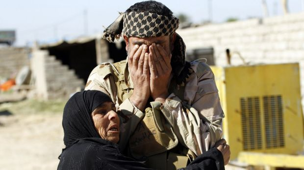 A resident welcomes a relative who belongs to the Popular Mobilisation militias  in the town of al-Alam on Tuesday.