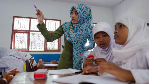 Class action: A teacher and pupils at a school run by anti-trafficking NGO Yayasan Kusuma.