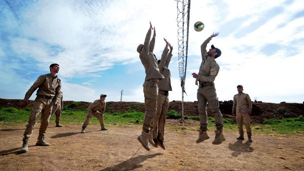 New conscripts to Rojava's army play volleyball during a break from training at an abandoned Syrian military base near ...