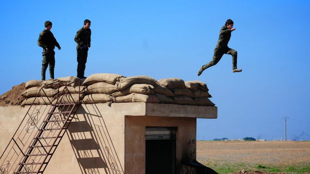 Three young YPG fighters prepare to leap from their lookout near the village of Tel Marouf, freed from the Islamic State ...