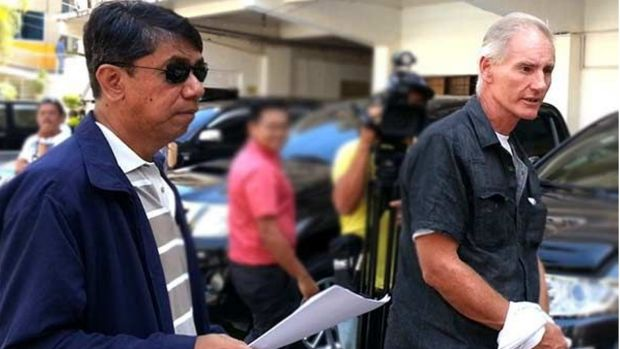 Peter Gerard Scully is escorted to court by agents of the Philippines National Bureau of Investigation before his ...