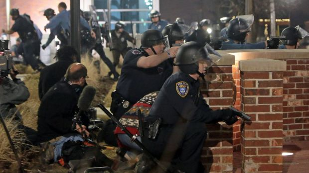 Police take cover after two officers were shot while standing guard in front of the Ferguson Police Station.