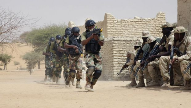 Nigerian special forces run past Chadian troops during a hostage rescue exercise.