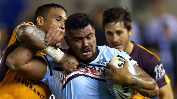 Shark net: Cronulla's David Fifita is wrapped up by Justin Hodges.