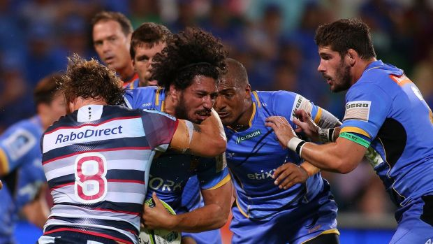 Rough and tumble: Sam Wykes of the Force is tackled by Scott Higginbotham of the Rebels.