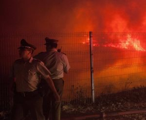Red alert: Police officers standby while a forest fire burns the hills of Valparaiso.