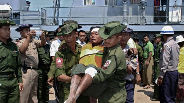 A survivor from a ferry accident in Myanmar that claimed at least 33 lives is carried by two Myanmar army soldiers from ...