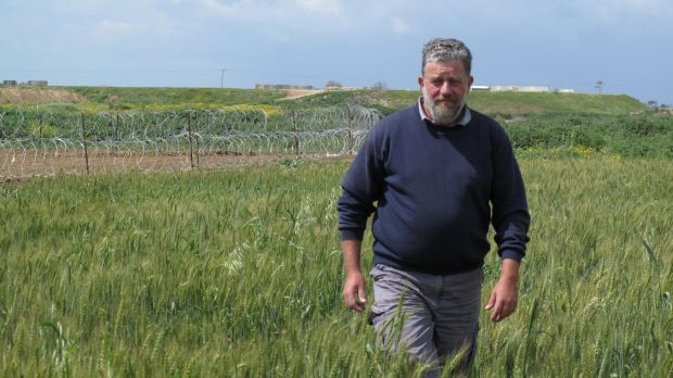 Pablo Leffler stands in the farmlands of Kibbutz Ein HaShlosha. The structures and razor wire behind him surround the ...