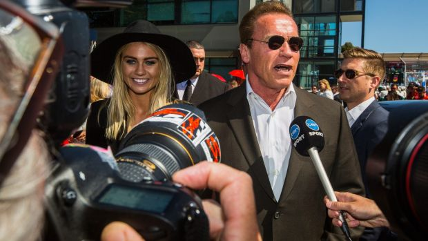 Arnold Schwarzenegger and model Elyse Knowles arrive at the Australian Grand Prix.