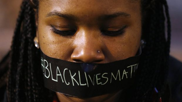 A protester wears tape over her mouth during a silent demonstration against what they say is police brutality after the ...