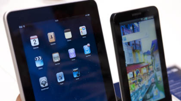 A journalist compares the new Samsung Galaxy Tab, right, with the Apple iPad, left.