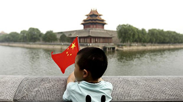 A boy holding a Chinese national flag stands outside the Forbidden City in Beijing.