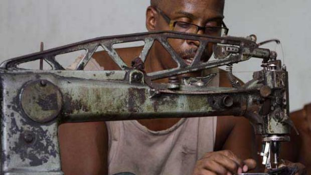 Manuel Cardenas repairs shoes in La Habanera state-run workshop in Havana, Cuba.