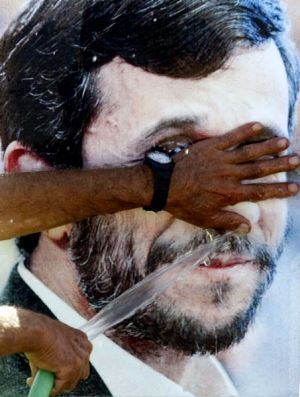 Clean face ... a man uses a hose to wash an image of Mahmoud Ahmadinejad at Maroun al-Ras in southern Lebanon as the ...