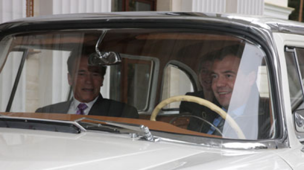 Dmitry Medvedev takes Arnold Schwarzenegger for a spin in a Soviet Chaikain car.