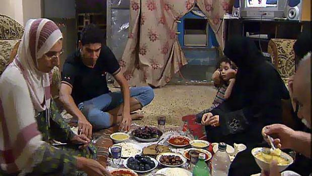 Zaheda Salem and her family eat an evening meal together on the seventh floor of an office building in Baghdad.