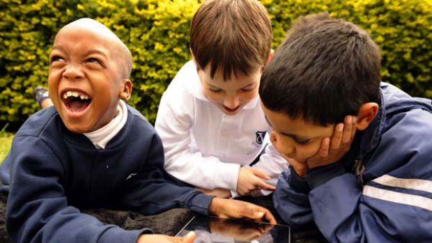 Excited Victorian College of the Deaf students (from left) Shadrak, Jacob and Samuel with an iPad yesterday. The college ...