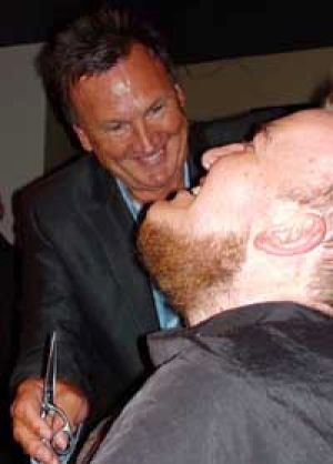 Tim Mathieson lends his hairdressing skills to shave off AAP journalist Peter Veness' beard at the National Press Club.